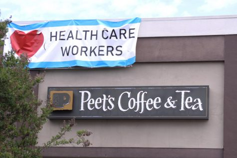 Above Peet's Coffee & Tea on Laurel Street flies a simple, yet meaningful, banner. The COVID-19 outbreak has prompted an outpouring of recognition for healthcare workers, many of whom risk their health to care for the sick.