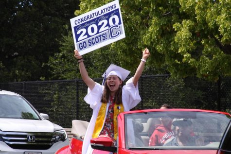 "Melina Dimick holds up a ""Carlmont Class of 2020"" yard sign and cheers as her family drives through the quad."