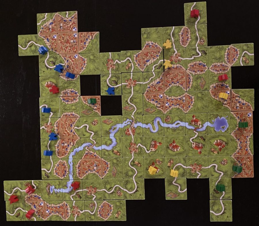 During the game, players connect roads, cities, and fields as they place tiles and build Carcassonne.