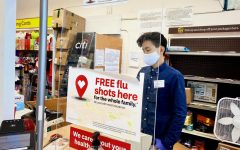 Joshua Sun, a junior and employee at CVS Pharmacy, checks a customer out while following the appropriate safety precautions.