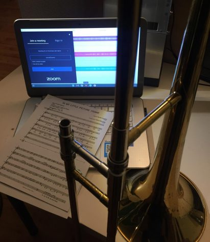 A computer open to Zoom and Soundtrap with sheet music and a trombone next to it.