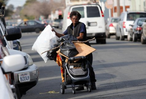 Patty Smith, a homeless man, carries his belongings to another location in Richmond, Calif.