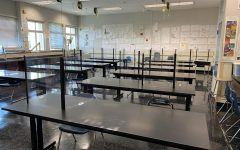 A classroom at Carlmont High School demonstrates precautions being taken for educational cohorts. It has plexiglass partitions at each desk, with seats measured 6 feet apart from each other.