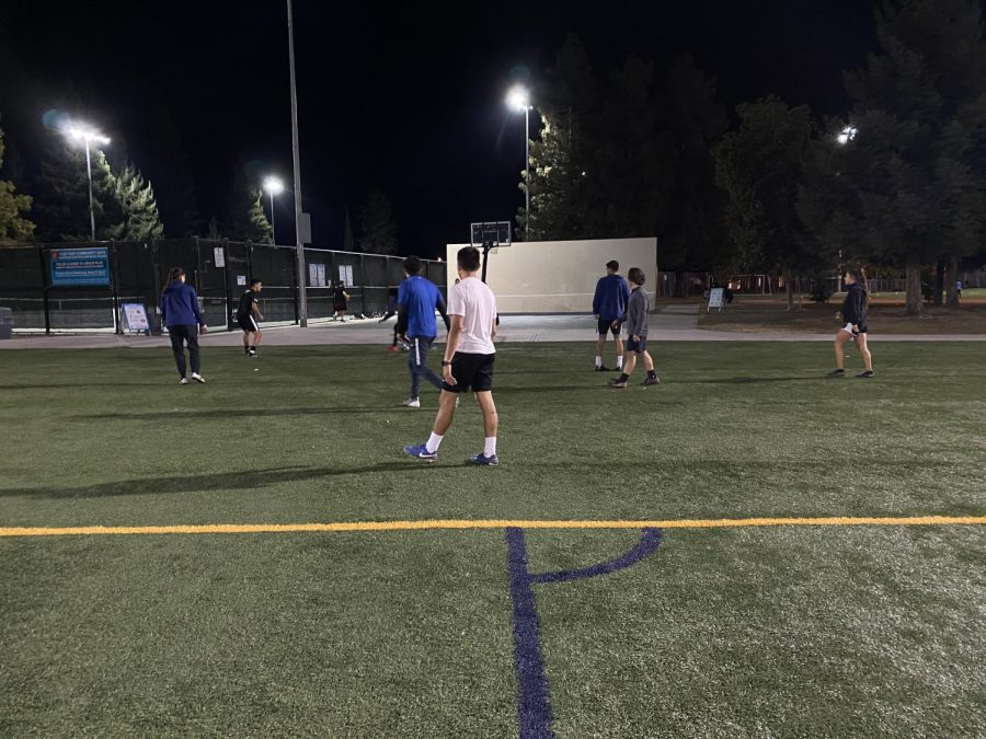 A group of people play in an unsanctioned pickup soccer game, wearing no face coverings and not practicing social distancing.