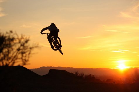 Matteo Saisi, a sophomore, does a table over a sunrise-lit jump at the Carlmont Jumps.