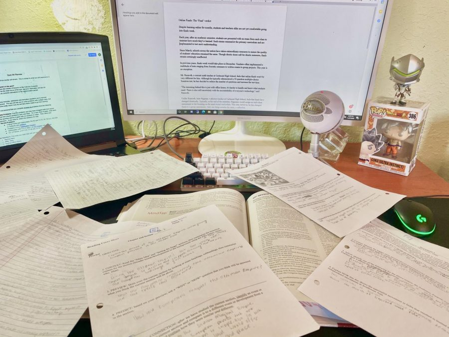 A student's desk is filled with study guides and review sheets as he studies for finals.