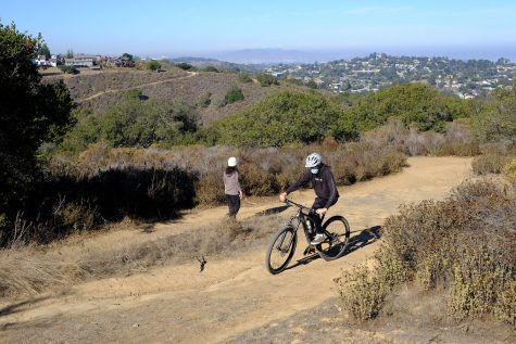 A biker and a hiker cross paths on Rambler Trail in Water Dog Lake Park.
