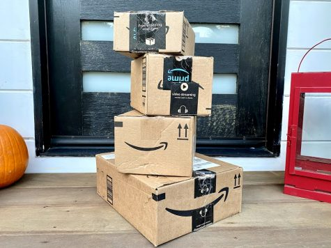 A stack of Amazon boxes on the front porch of a home.