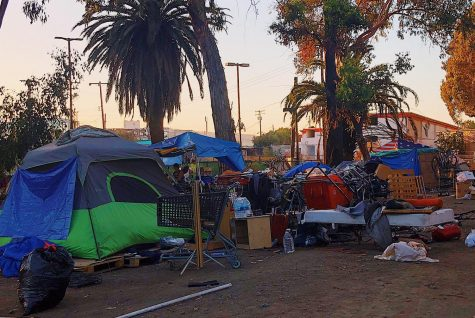 People rest at a homeless encampment under a freeway in Redwood City. The camp is filled with tents, shopping carts, makeshift shelters, and trash.