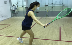 Aanika Tiwary raises her racket as she prepares to swing and hit the ball against the wall.