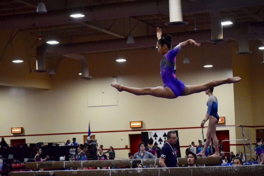 Soaring to new heights:  Ayumi Oshiro flies across the balance beam at a gymnastics competition.