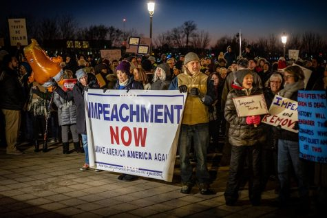 Protestors gather during a rally, calling for the impeachment of President Donald Trump.