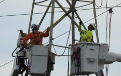 Two Pacific Gas and Electric (PG&E) workers hook a wire to an electrical tower near the Redwood Shores Levee.