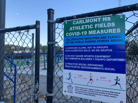 The gates to enter into the Carlmont football stadium display the COVID-19 field restrictions.