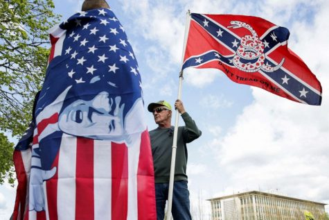 A right-wing protestor holds a flag that combines a Gadsden flag from the American Revolution with a Confederate flag from the Civil War. Though the two symbols, historically, contradict each other, they are now frequently seen together. He talks to another man holding an American Flag with President Trump's face plastered over it.