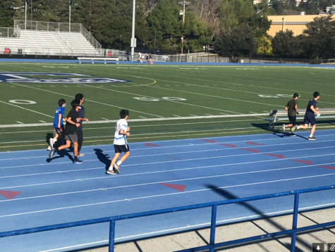 Carlmont cross country athletes run around the track as a team.