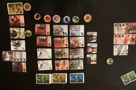 The end of a game of Splendor. Note that there are three rows of cards for the different development levels, nobles above those, stacks of gem tokens in the supply, and gem tokens and purchased cards in each player