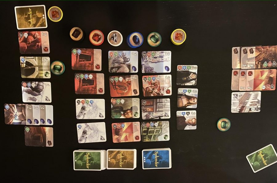 The end of a game of Splendor. Note that there are three rows of cards for the different development levels, nobles above those, stacks of gem tokens in the supply, and gem tokens and purchased cards in each player's area.