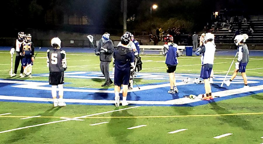Todd Irwin, coach of the boys varsity lacrosse team, gives the players advice on  how to correctly position themselves on the field.