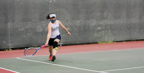 A Carlmont player strikes the ball during her match against Woodside.