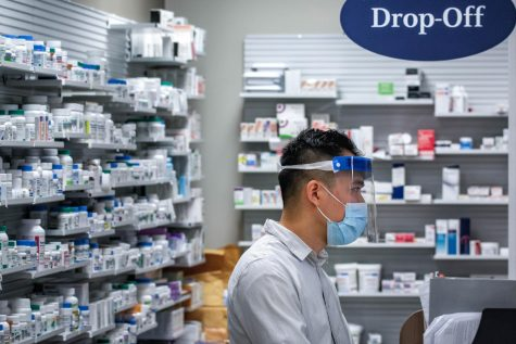 A pharmacist assists customers during the pandemic, fulfilling an essential service that has recently received supplemental hazard pay in some cities in the Bay Area.