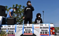 A speaker stands on a truck bed in California, addressing a crowd that had gathered for a protest in support of hazard pay mandates.