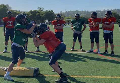 JV players John Griffith and Chris Campbell practice tackle drills during a three pod rotation circuit.