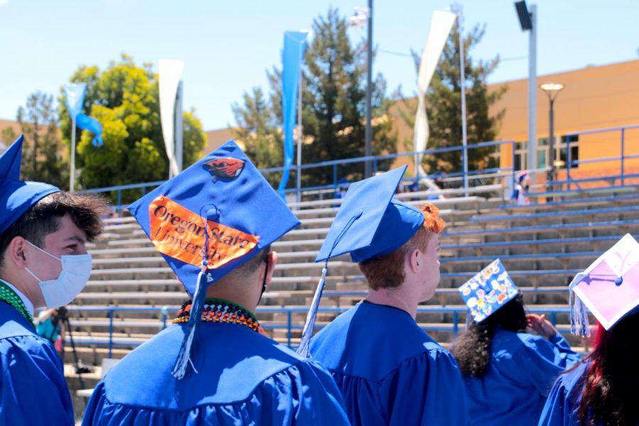 Graduates sport their future plans, including colleges, on the back of their graduation caps.