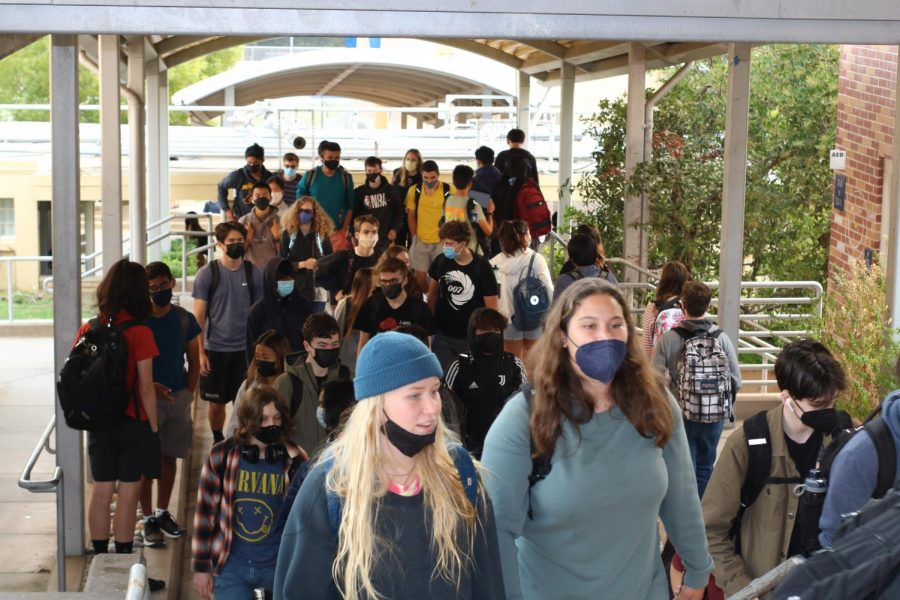 Students crowd the outside stairways as they walk to their first period from the quad. There is no masking requirement outside.