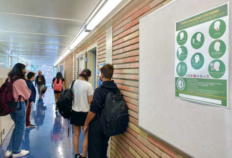 Students line up by a COVID-19 health sign to enter the office.