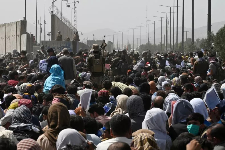 Afghans gather on a roadside near the military part of the airport on Friday in hopes of fleeing the country after the Talibans takeover.