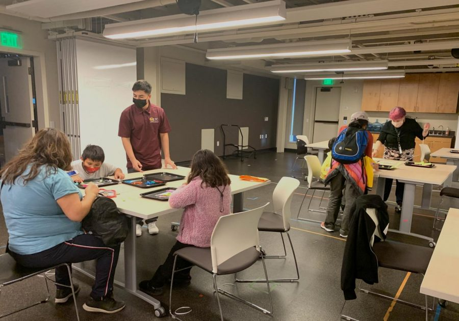 SPHE volunteers work at the glow copter station to help visitors assemble miniature paper copters with LEDs to teach basic electrical engineering.