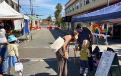 A child excitedly picks out a balloon animal at the farmers market.