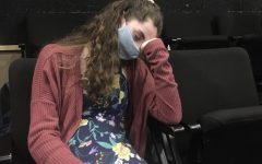 A student leans on their wrist as they start to fall asleep in class.