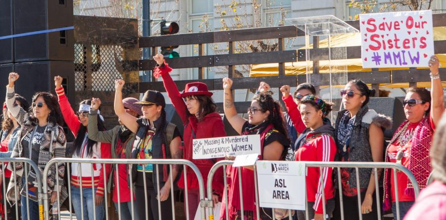 Womens March San Francisco attendees raise fists and hold signs in support of missing and murdered Indigenous women in 2018.