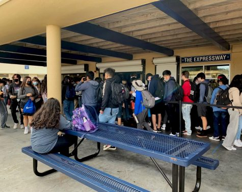 Dozens of students wait in line to receive their lunches.