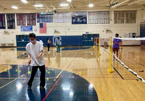 Joshua Ting, a junior, serves the birdie in a practice match at a Carlmont open gym.