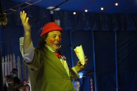 Nino the Clown, played by Giovanni Zoppé stands in the audience while telling a story to the crowd.
