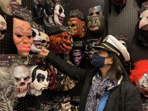 A customer shops for Halloween masks at a local Spirit Halloween store.