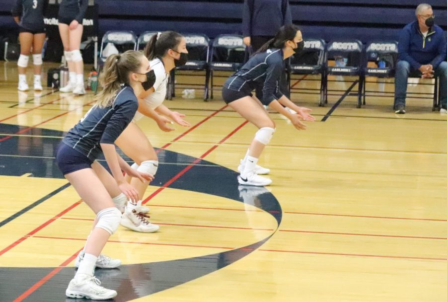 Calico Przybyszewski, Isabelle Won, and Kianna Young stand ready to receive an incoming serve.