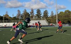 At an after-school practice, players run a drill to prepare their defense for the next game.