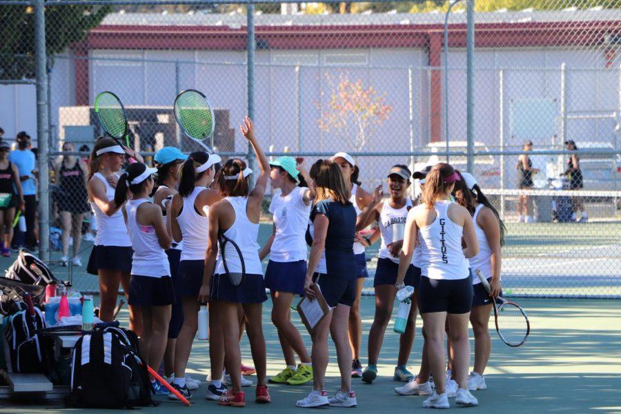 Carlmont girls varsity tennis huddles before the start of the game.