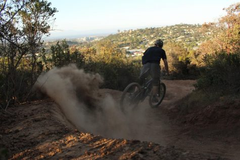 Eric Chuang, a senior, ride through an extremely dusty patch of trail.