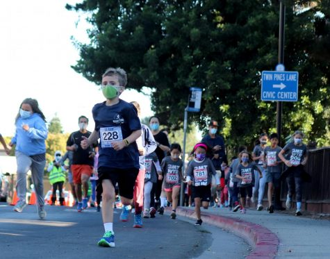 A participant of the kids' 1-mile race runs by Twin Pines Park.