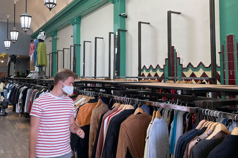 A man shops for clothes in Wasteland, a store that resells designer clothes. By giving the clothing a new owner, Wasteland cuts down on the waste that comes from the fashion industry.