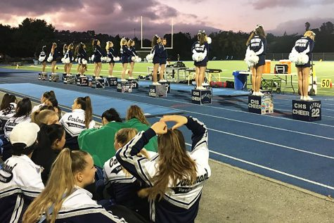 Cheerleaders line the edge of the football field during a football game in 2019.